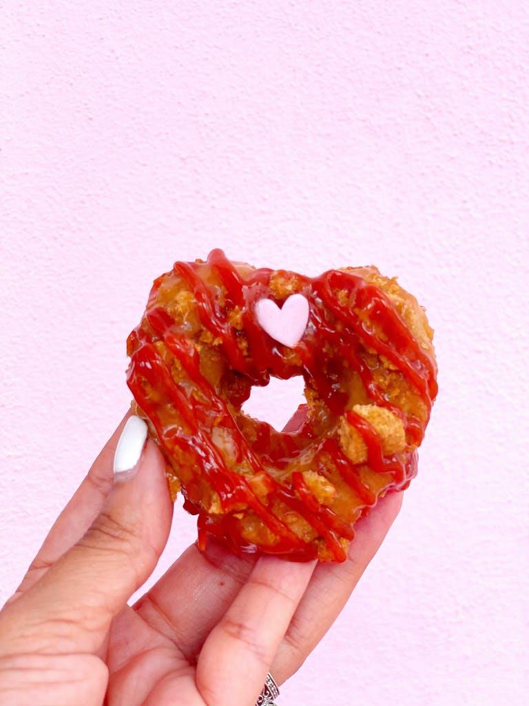 a hand holding a half eaten doughnut