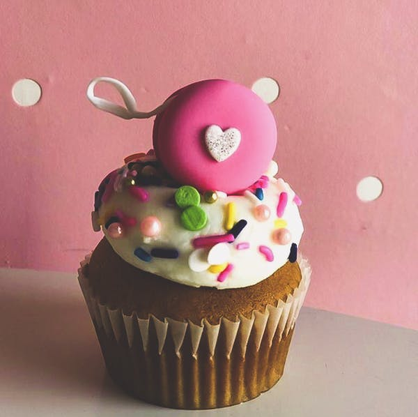 a closeup of a cupcake topped with sweet sprinkles and a heart shaped figure