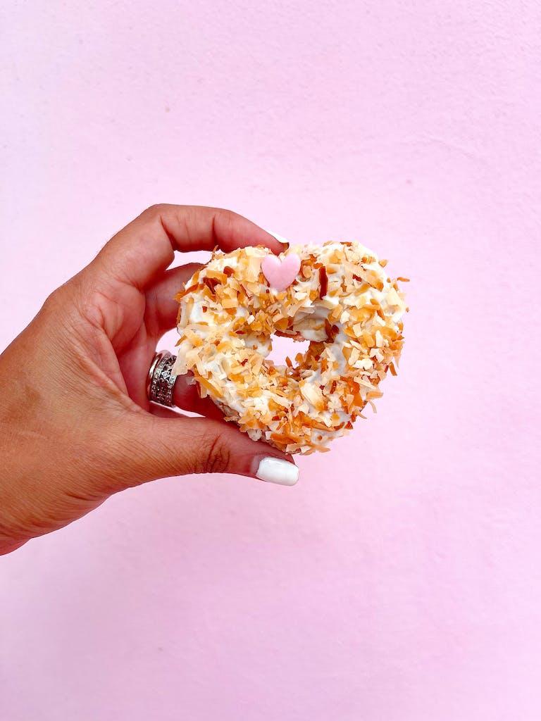 a hand holding a half eaten donut