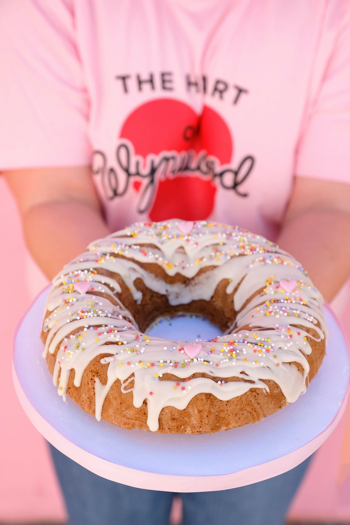 a close up of a person holding a donut in front of a cake