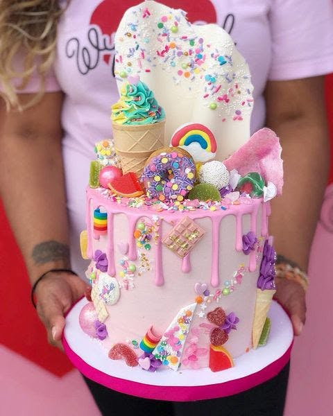 a little girl standing in front of a cake