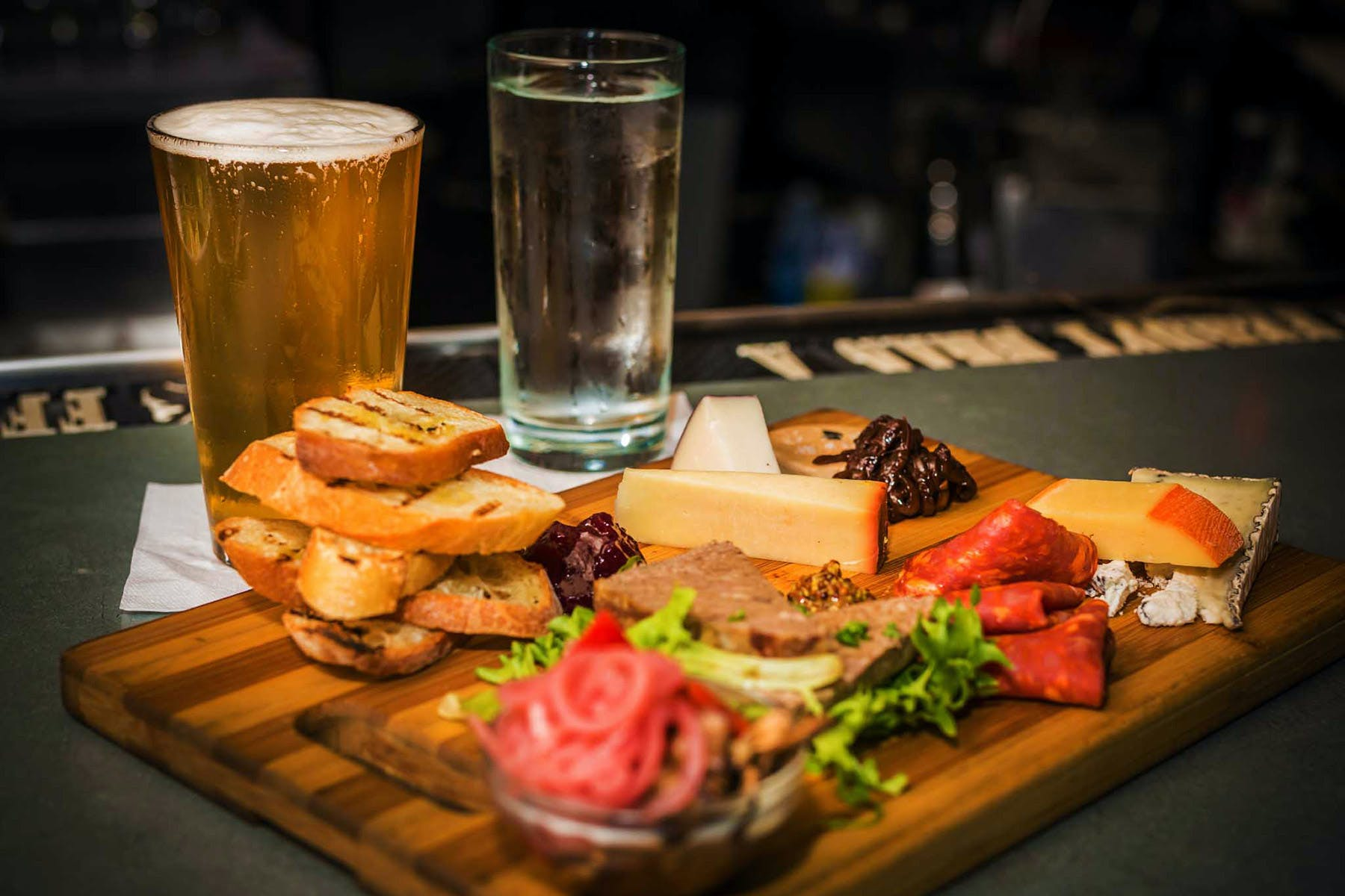 a glass of beer on a wooden cutting board