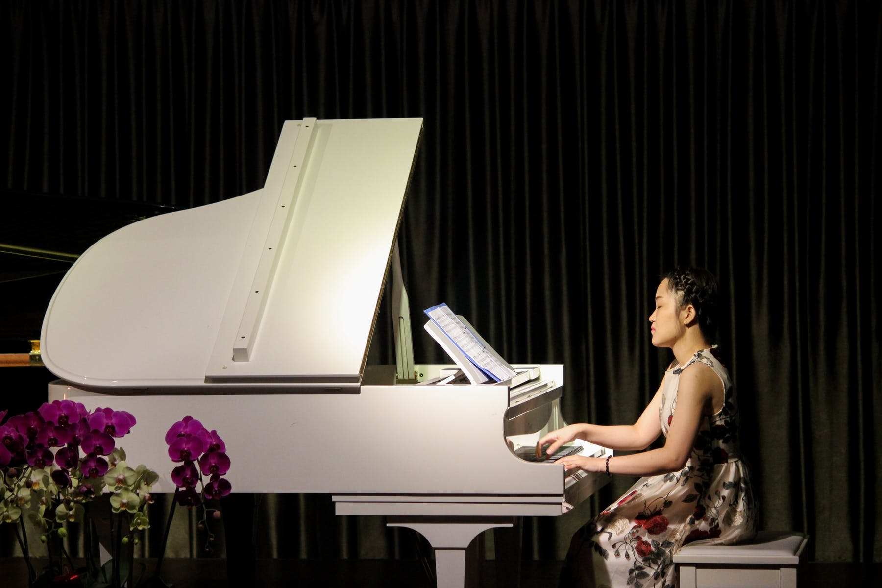 a woman playing a white piano