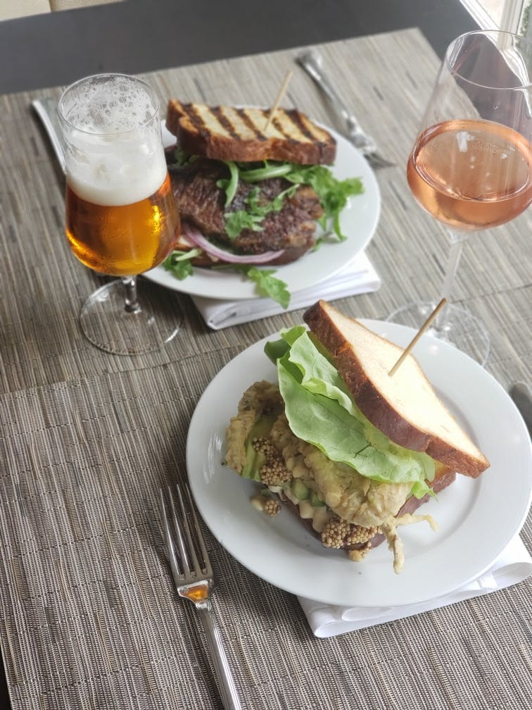 a table topped with a sandwich and salad on a plate