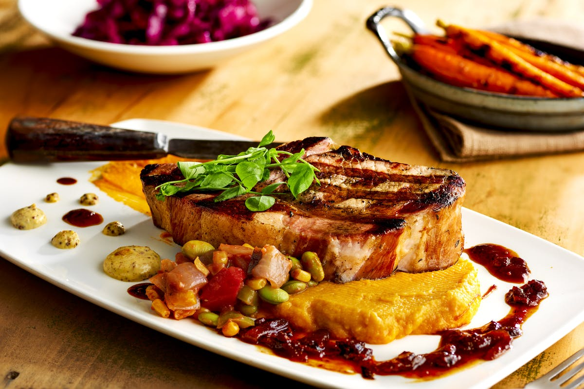 close up of a pork chop on a dish with various sides