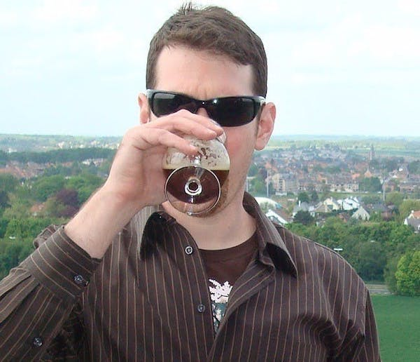 a man wearing sunglasses and holding wine glasses