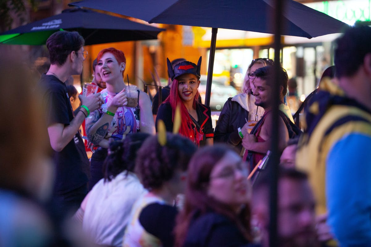 a crowd of people watching a colorful umbrella