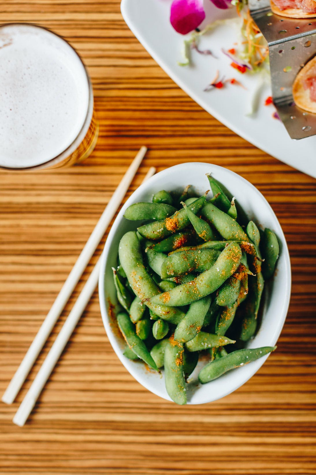 a bowl filled in with green peas sitting on a wooden table