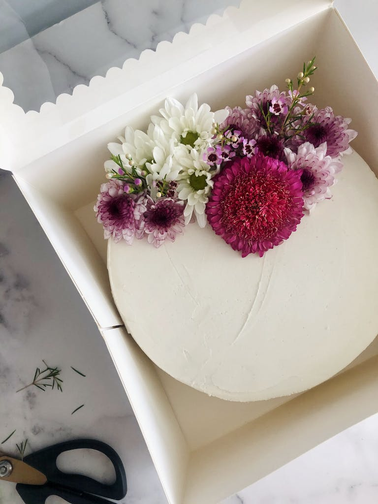 a flower sits in a cake in a box