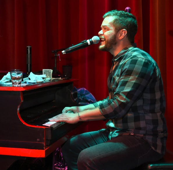 a man sitting on a stage with a piano