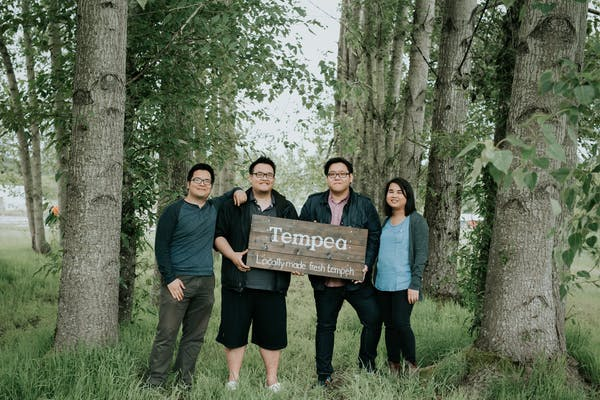 4 people holding a wooden sign that says tempea