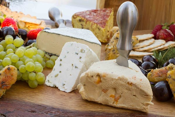 An array of different cheeses and grapes