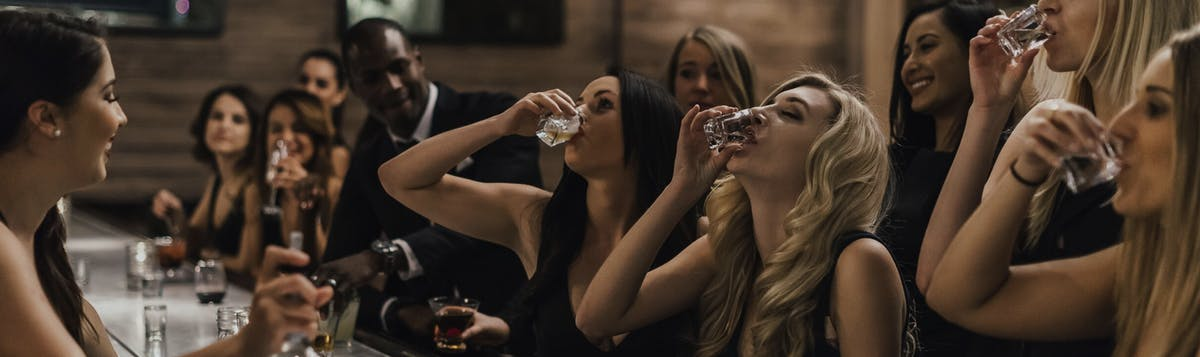 women at bar doing shots