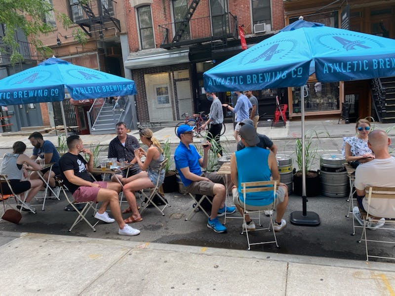 a group of people sitting at a table with a blue umbrella