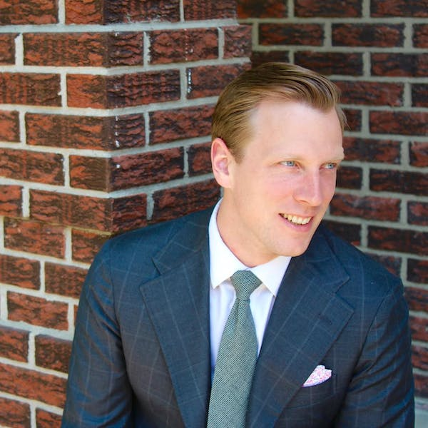 a man in a suit standing in front of a brick wall