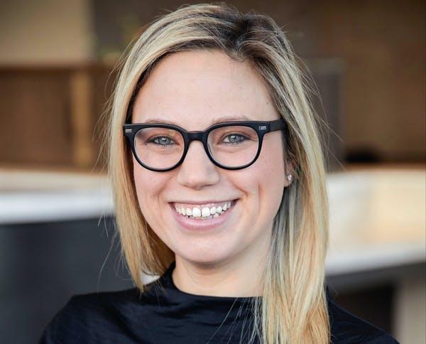 Gina-Marie Ciccotelli wearing a black shirt and glasses and smiling at the camera