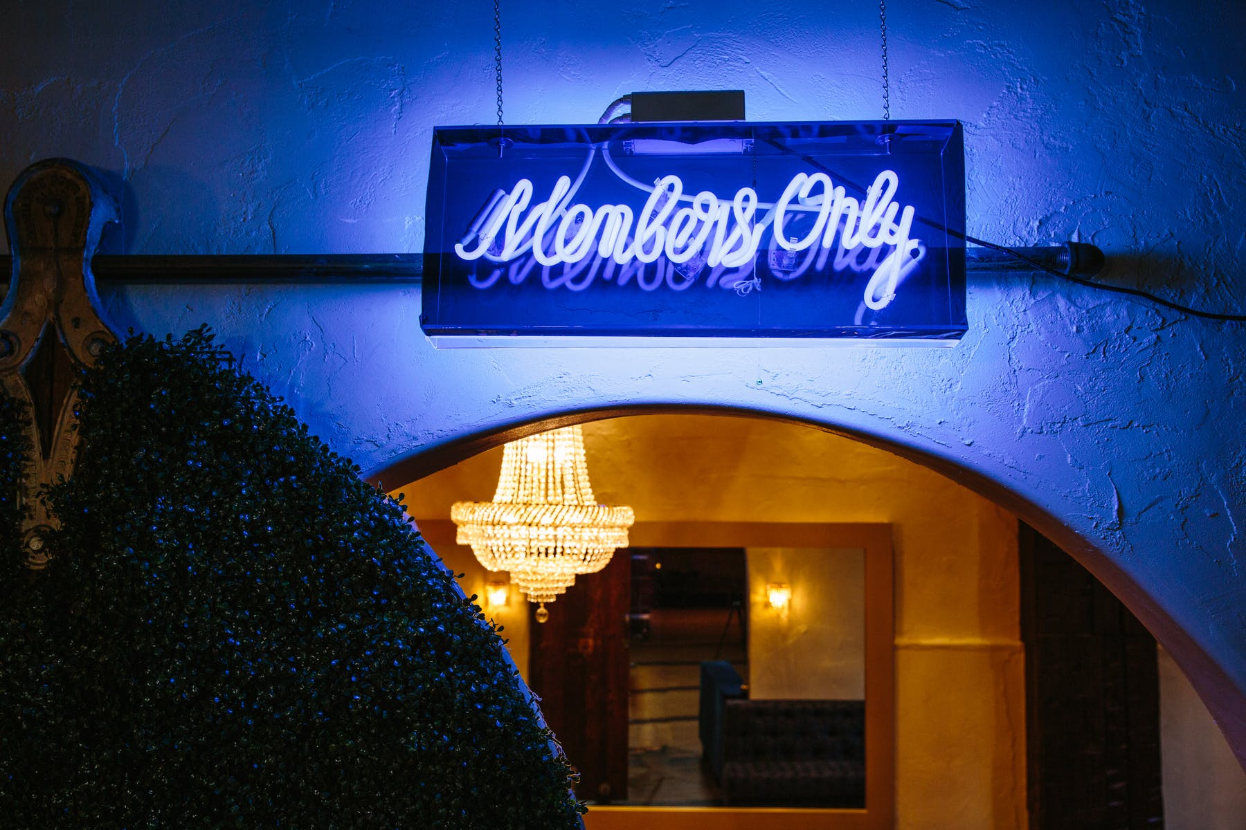 a blue neon sign above a bar entrance