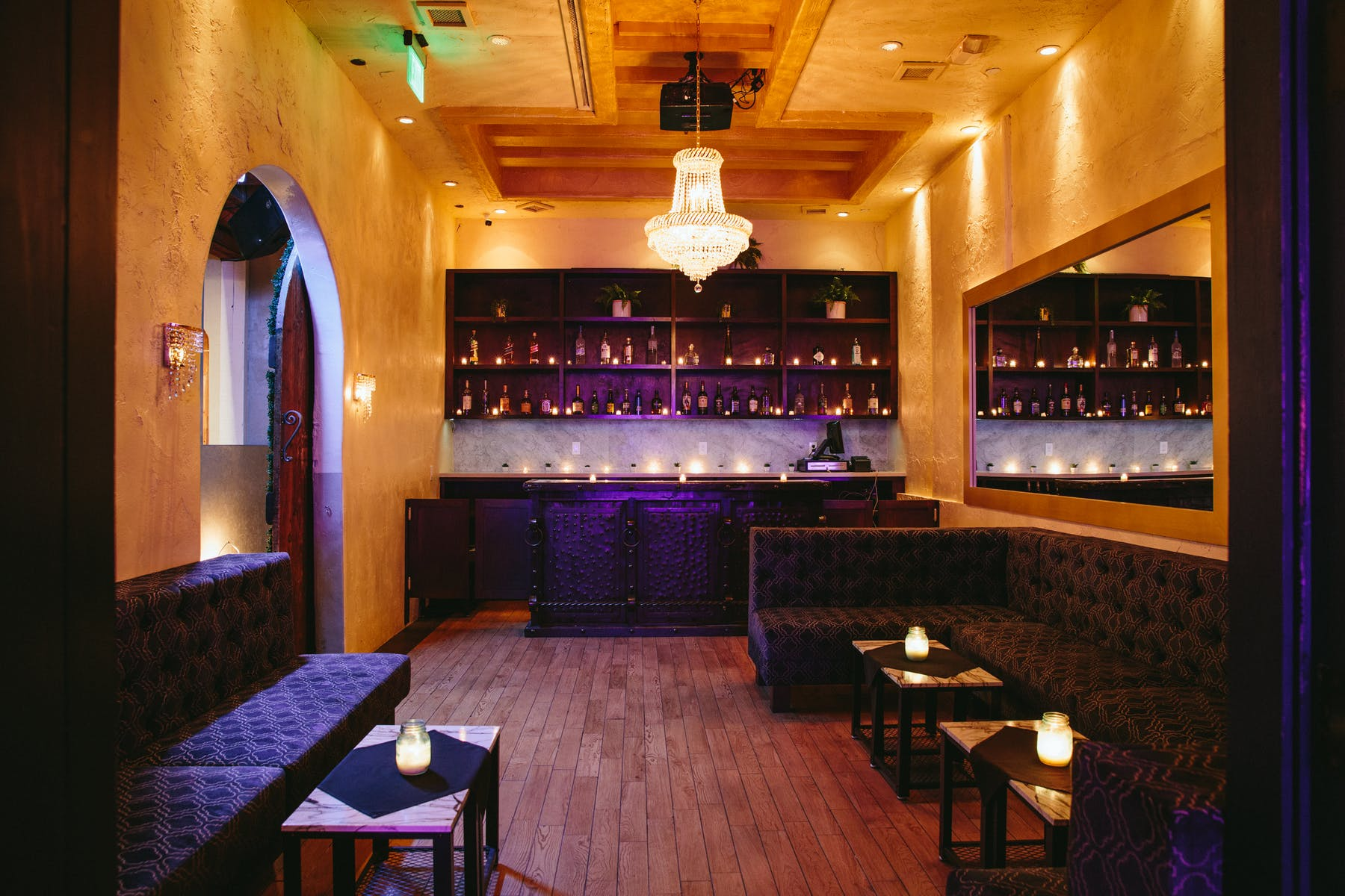 a big room with a bar, a shelf full of bottles, a table booth and a chandelier