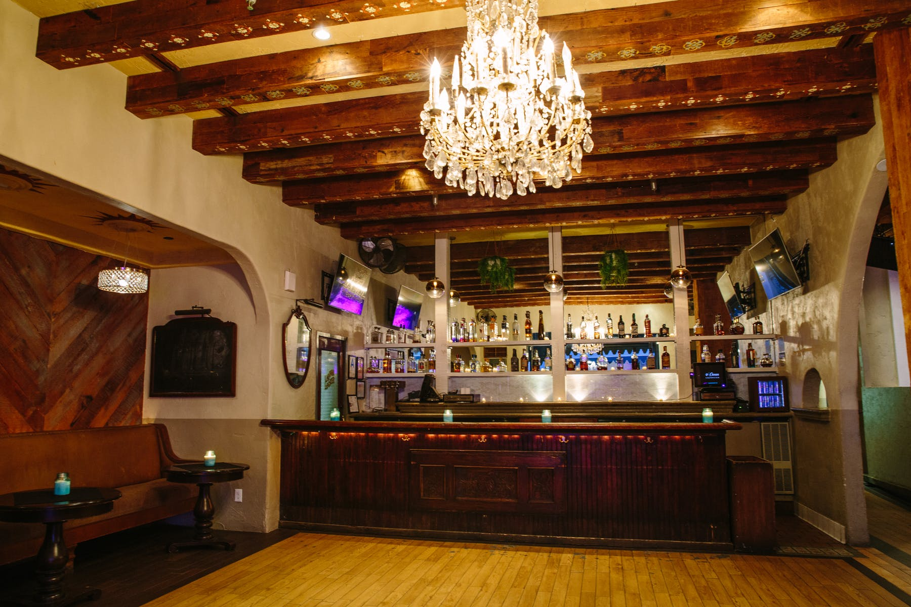 a large room with a yellow carpet filled with a bar, counter, a shelf topped with bottles and a chandelier
