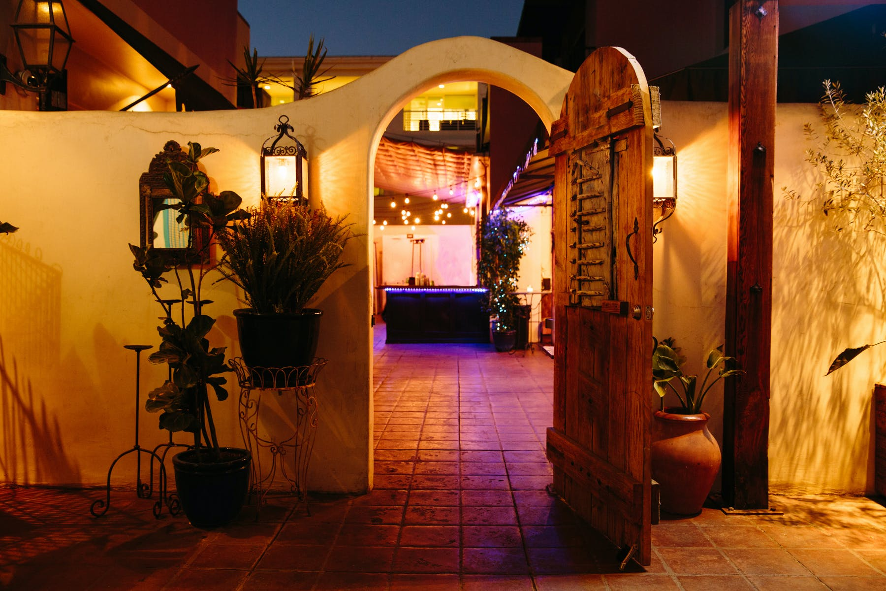 an entrance gate to an exterior patio litten up by a purple light