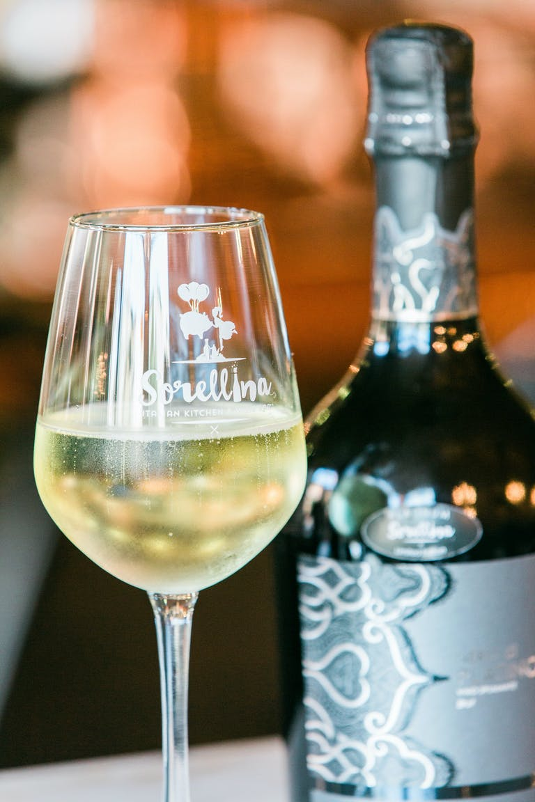 a close up of a bottle and a glass of wine