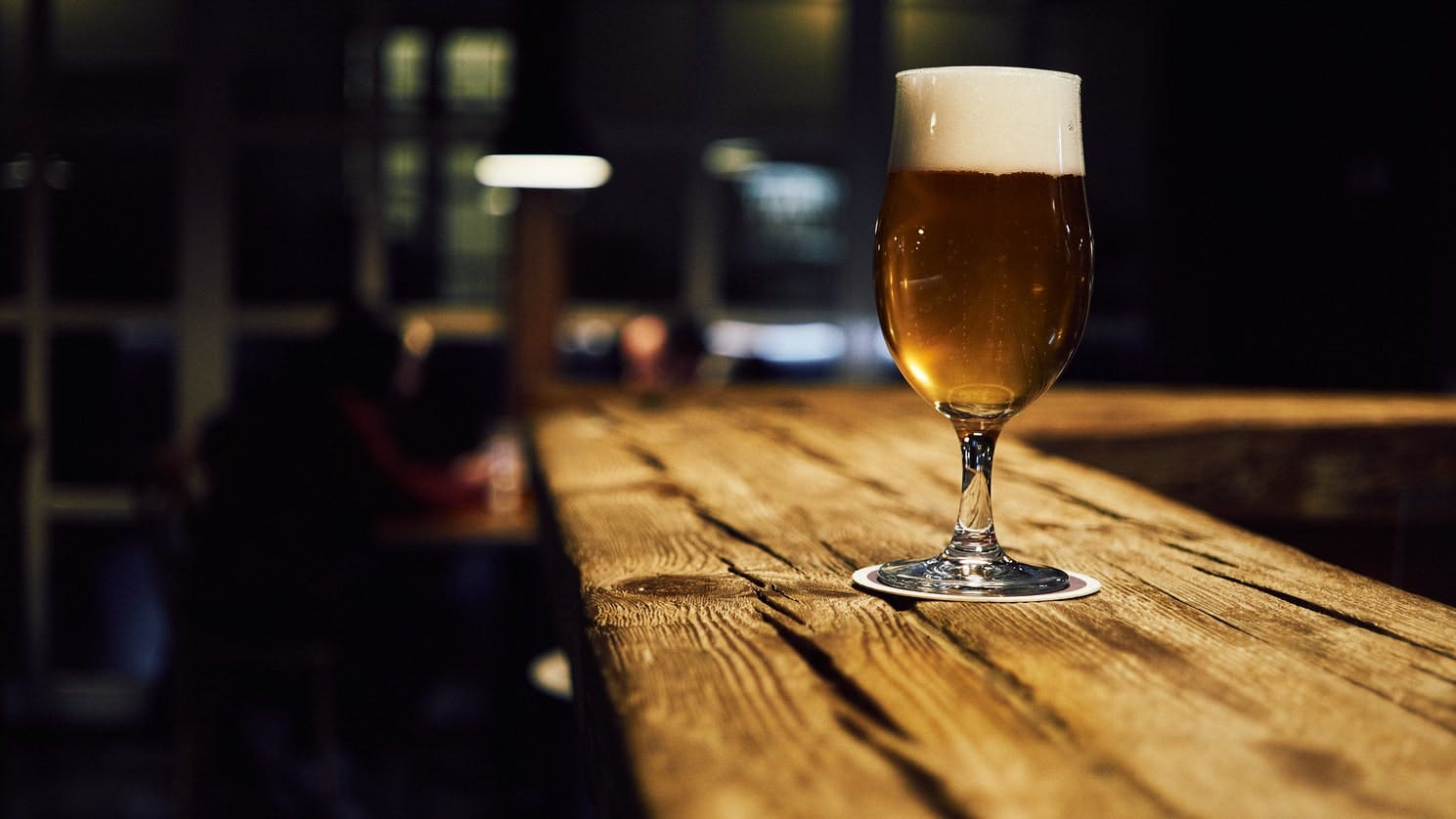 a glass filled with beer on a wooden table