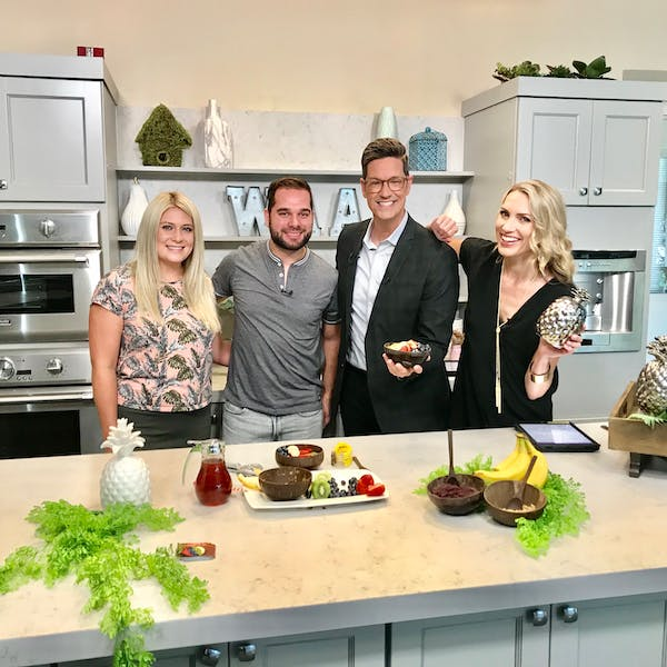 a group of people standing in a kitchen
