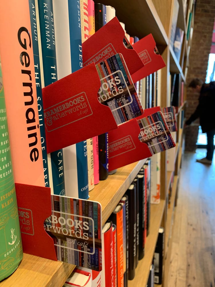 a stack of flyers on a table next to a book shelf