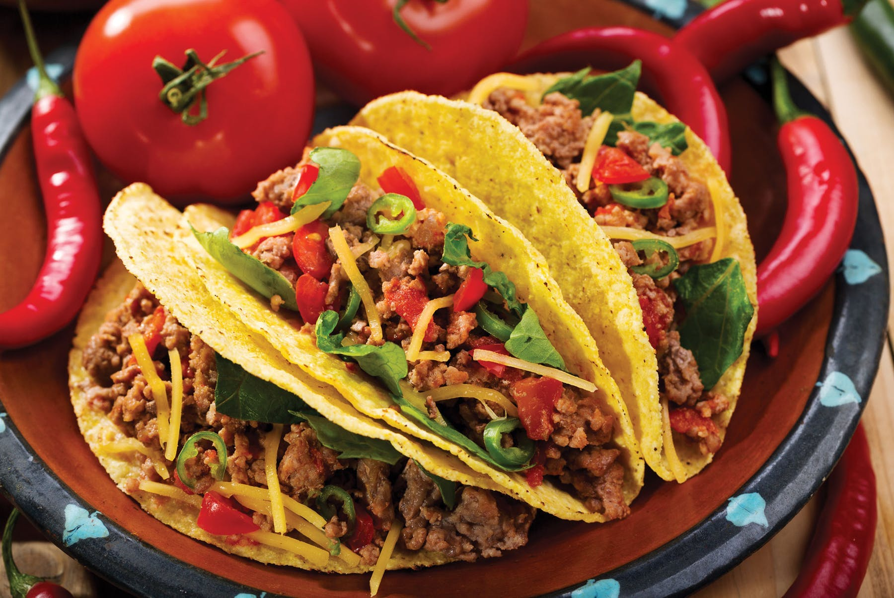 a close up of three tacos on a plate