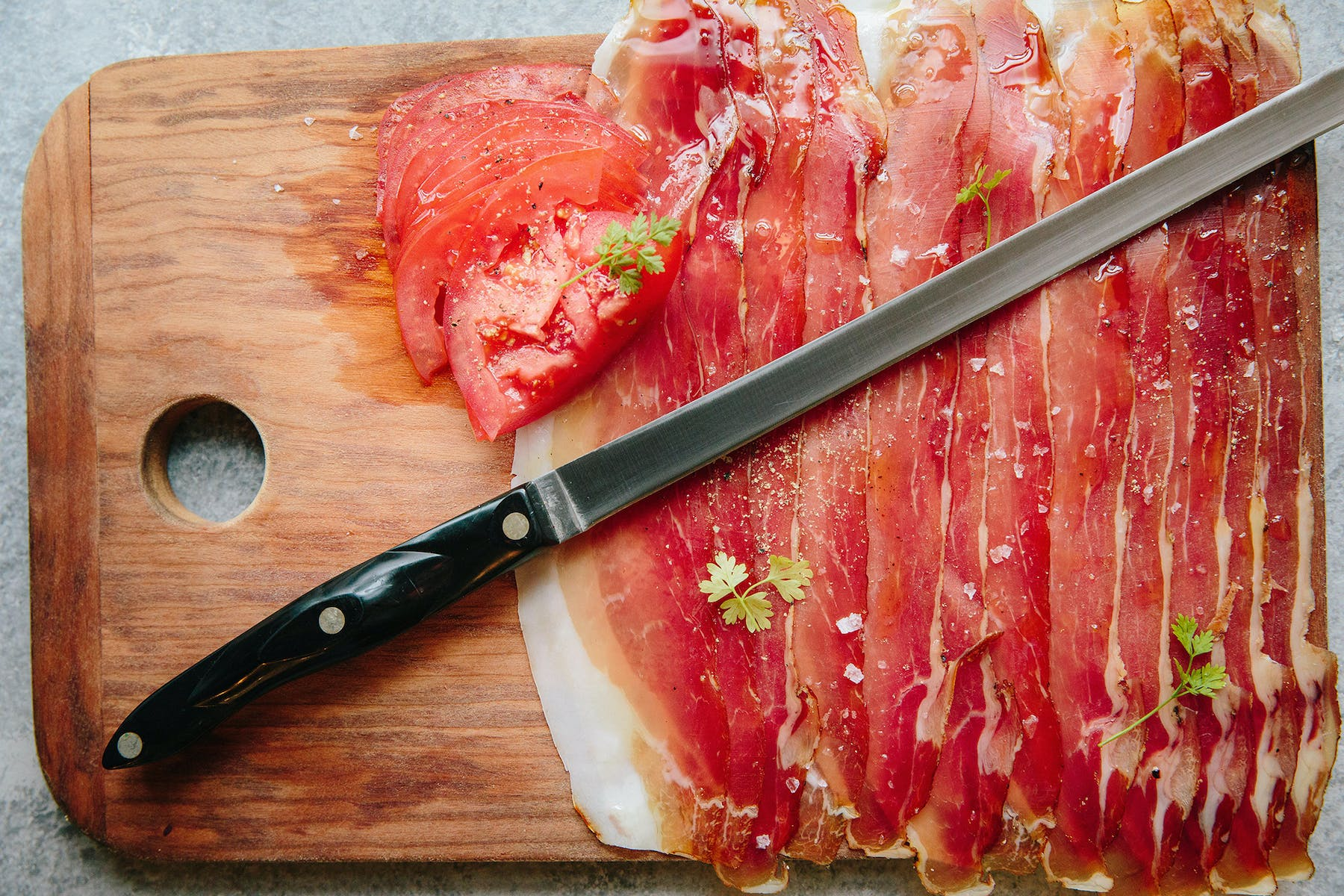 a cutting board with ham and a knife on top