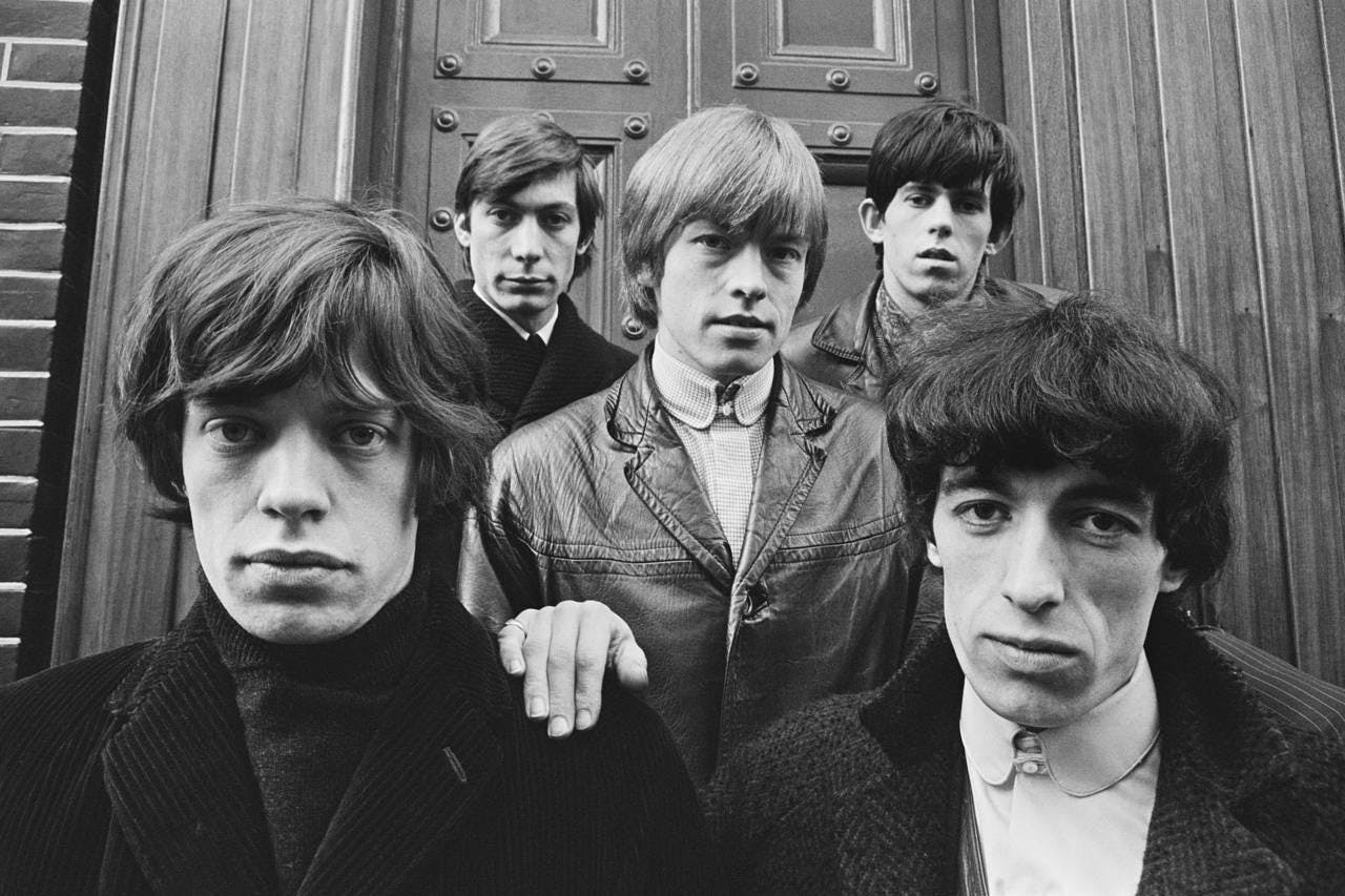 a black and white photo of Mick Jagger, Charlie Watts, Brian Jones, Bill Wyman posing for the camera
