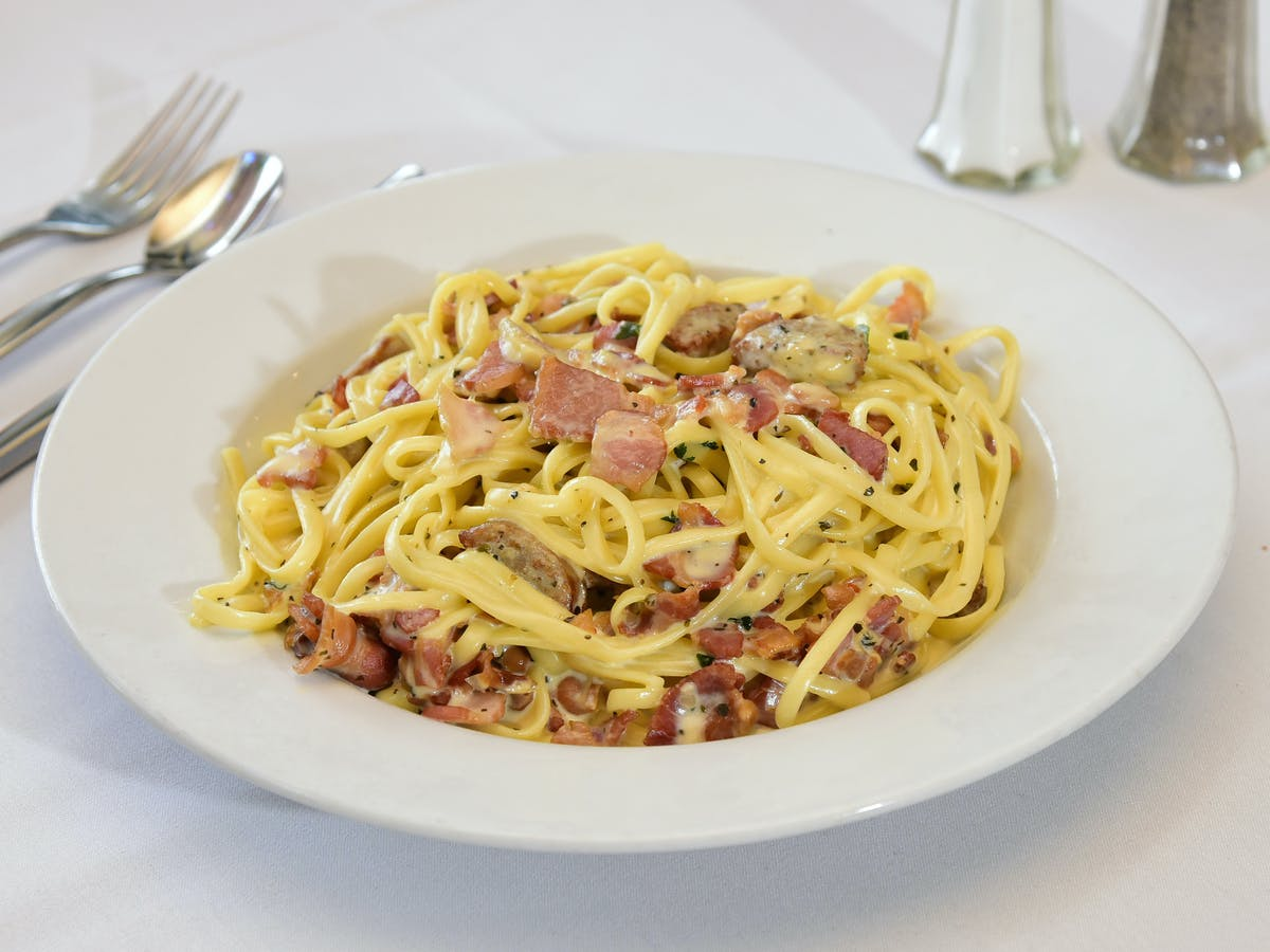 a white plate topped with pasta and vegetables