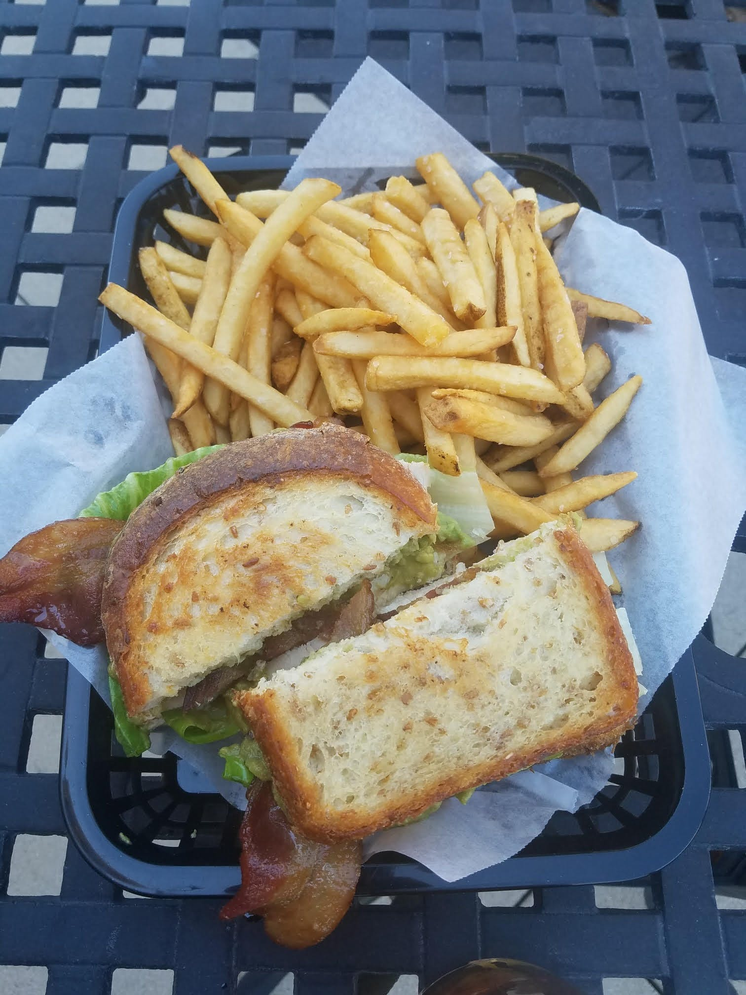 a sandwich sitting on top of a pile of fries