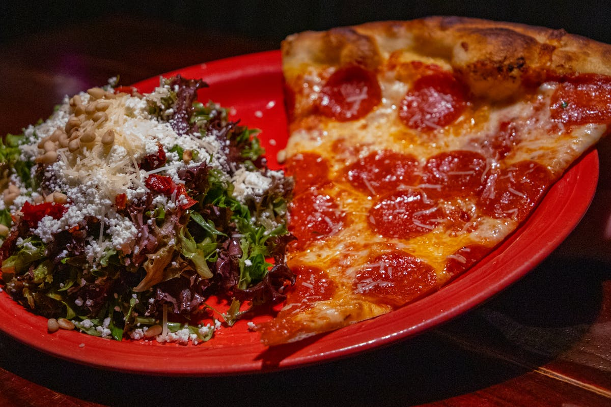a plate of food with a slice of pizza
