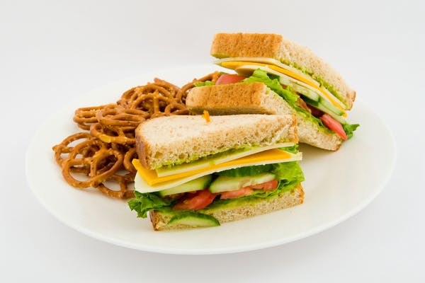 a sandwich cut in half sided with pretzels on a plate