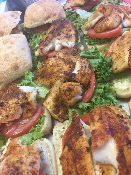 a close up of a stack of grilled chicken breast, lettuce, and sliced tomato