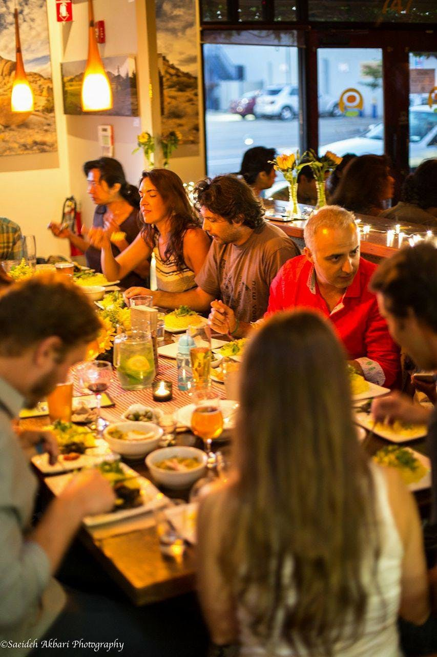a group of people sitting at a table in a restaurant