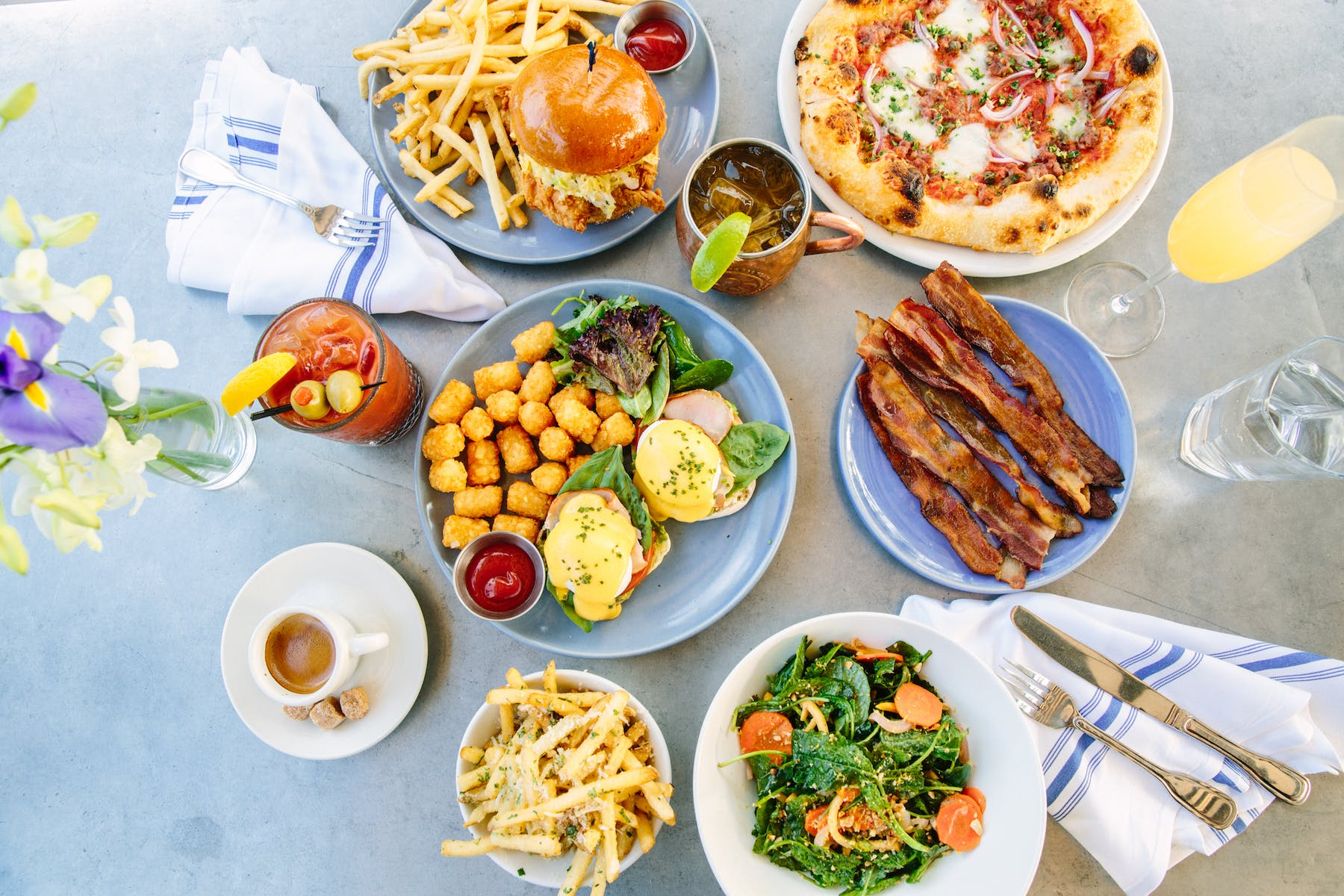 different plates of food hamburger, french fries, bacon, pizza served on a table