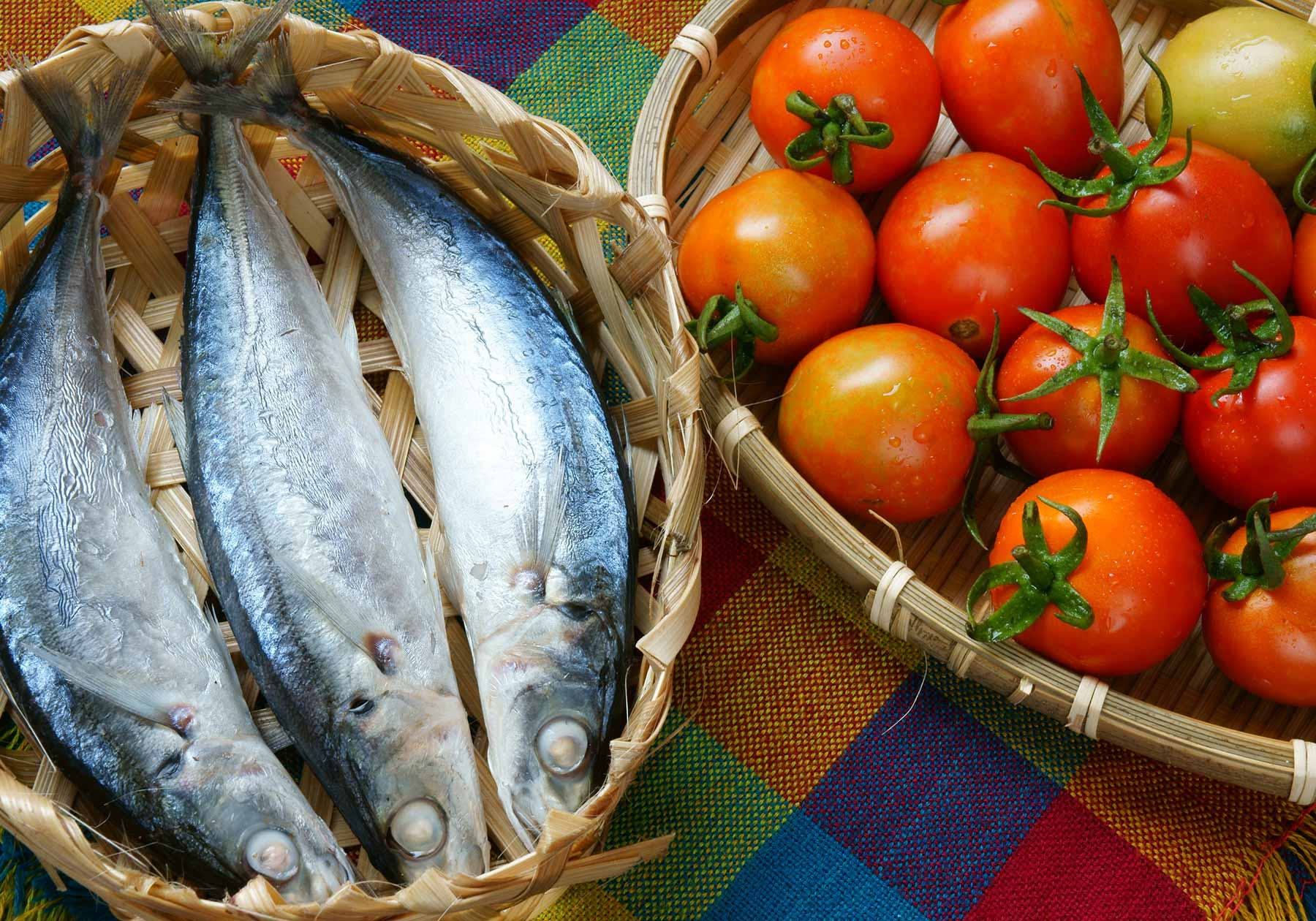 Baskets of fresh fish and tomatoes to represent French cuisine in French Polynesia and Vietnam.