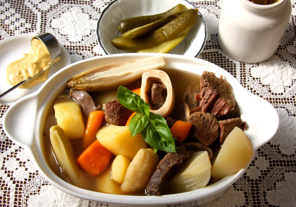meat, potatoes, and vegetables in a bowl of broth