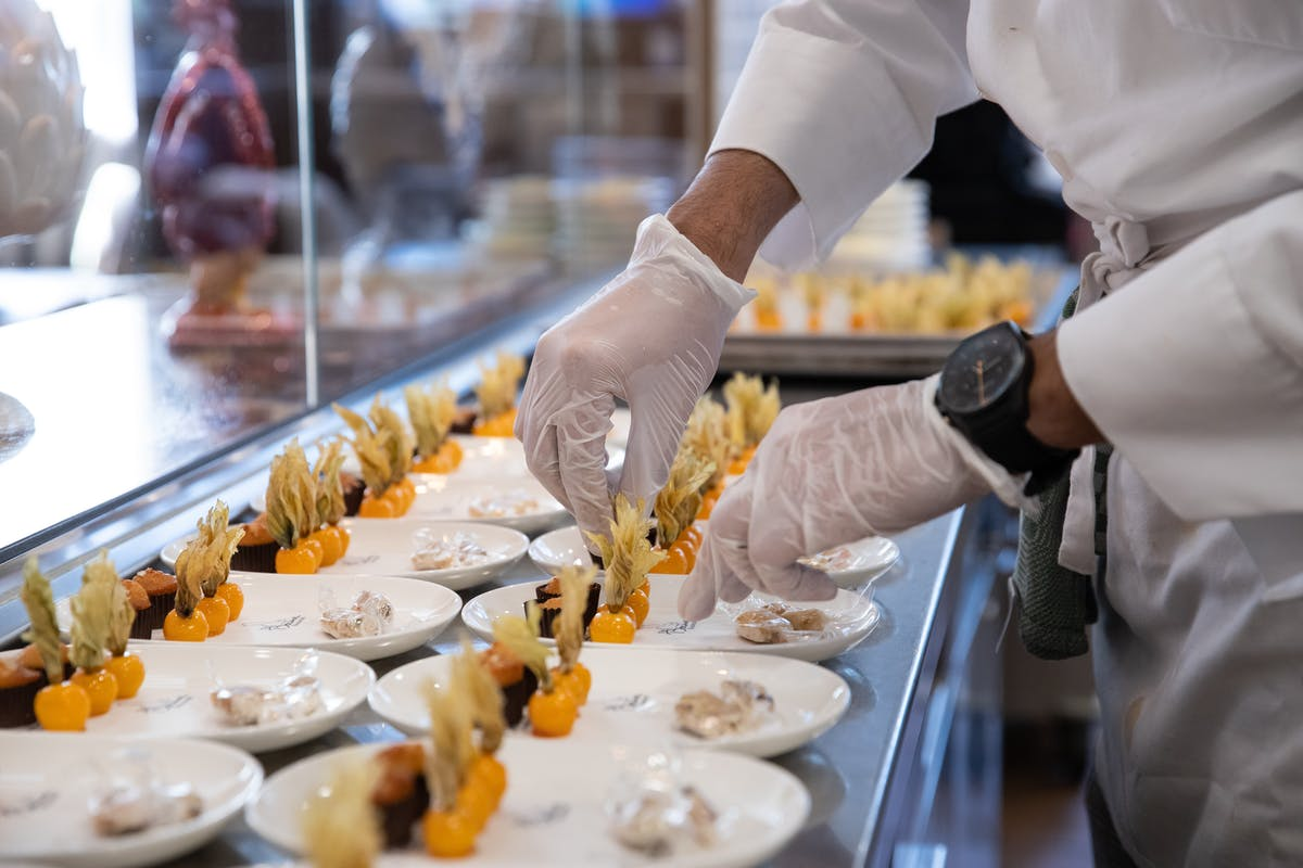 Chef preparing food on plates at the Bocuse Restaurant at the CIA in the Hudson Valley.