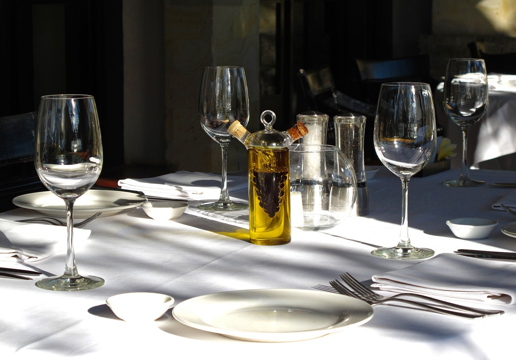 a table set with white plates, empty wine glasses and silverware
