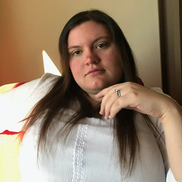 a woman sitting on a bed posing for the camera