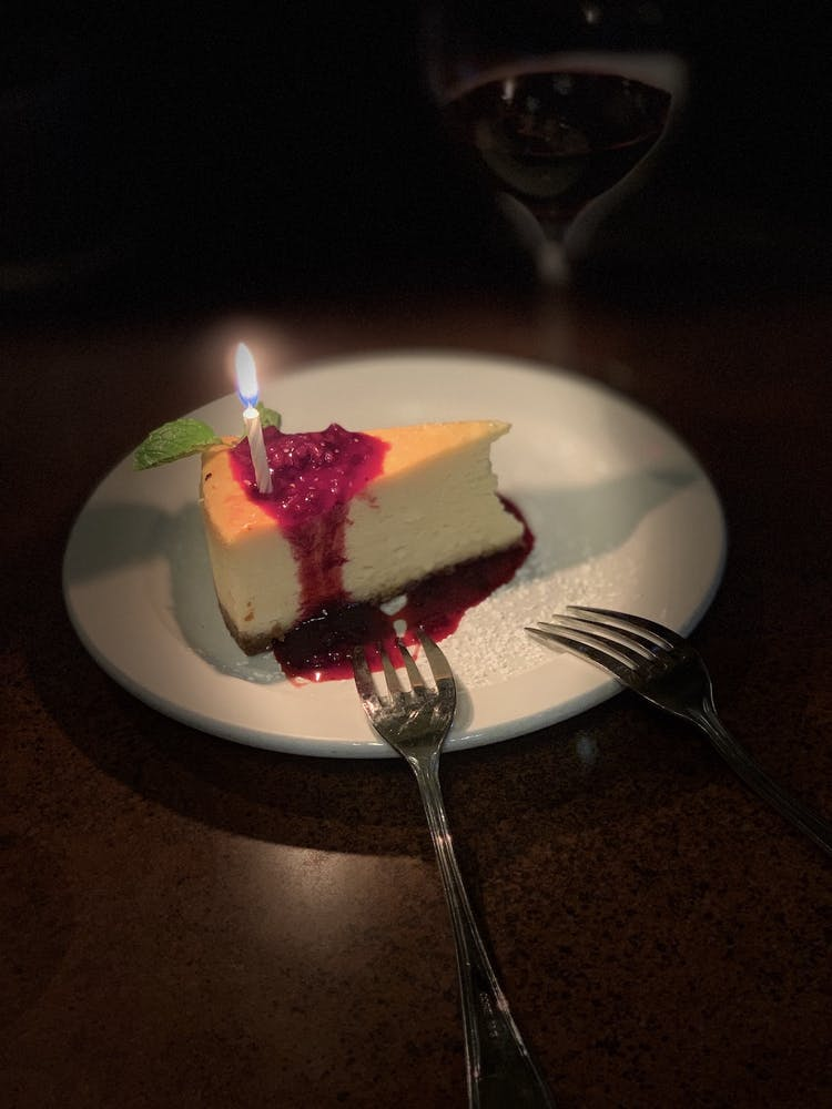 a plate with a birthday cake with lit candles