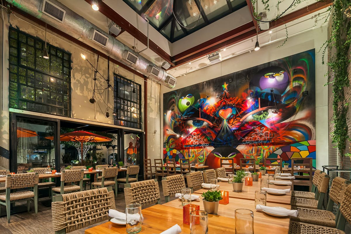 a restaurant dining room with a drawing as a background