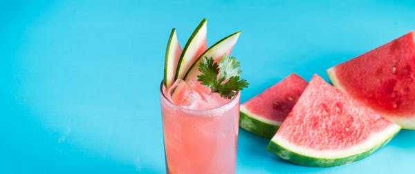 a close up of a drink with watermelon slices next to it