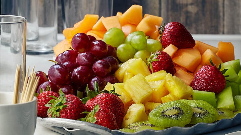 a plate is filled with fresh fruit and vegetables in a cup