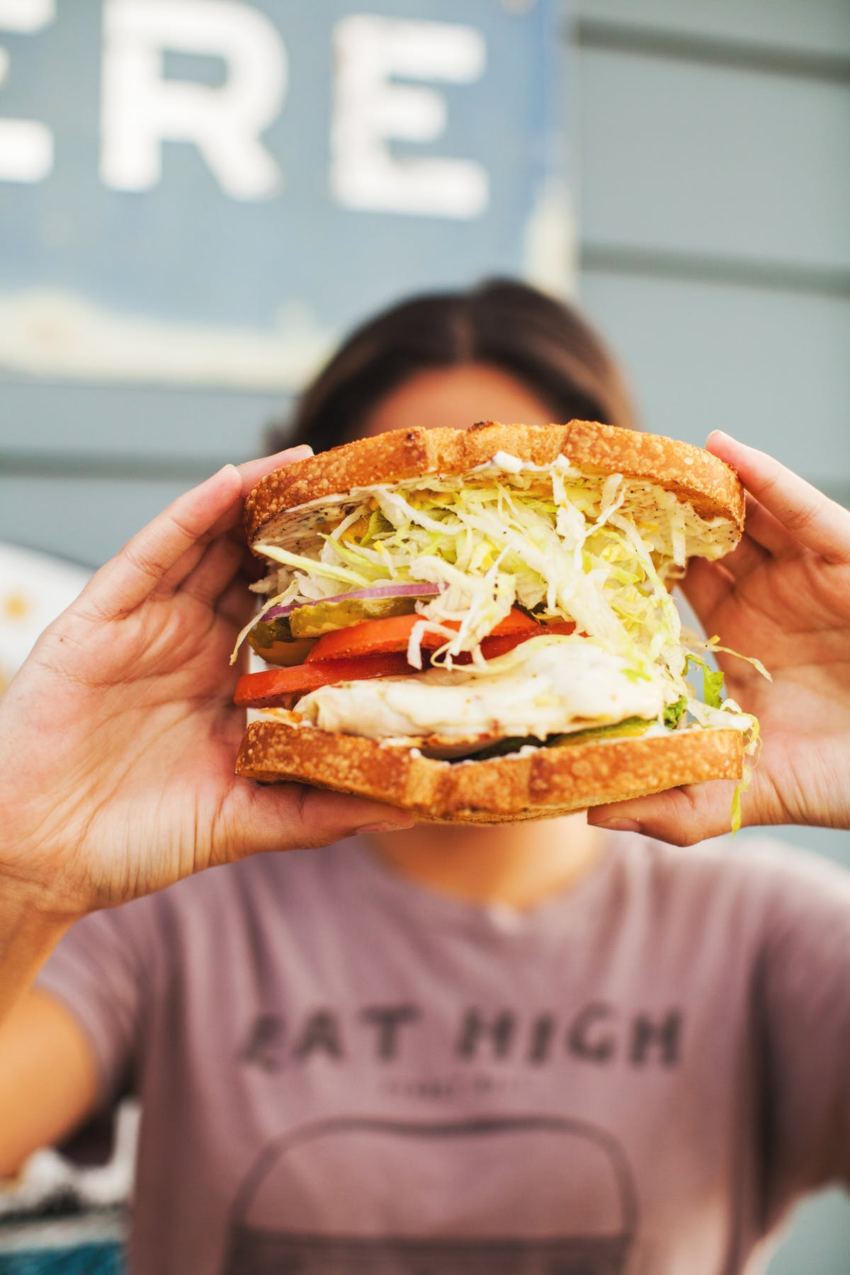 a person holding an enormous sandwich