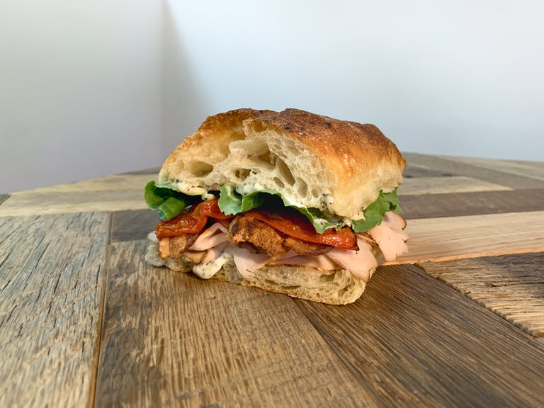 a turkey club sandwich sitting on top of a wooden table