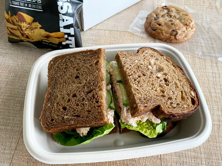 a salmon rillettes sandwich in a box on a table